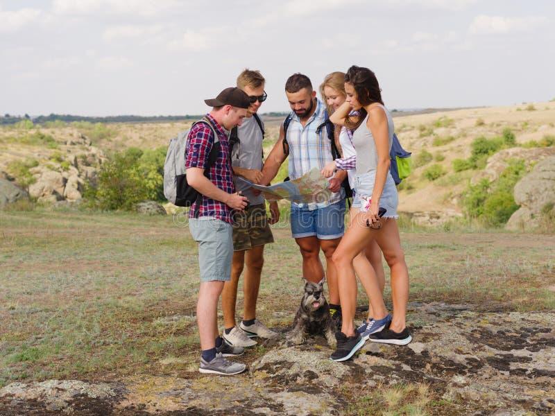 Turistas que miran una correspondencia Mapa de la demostración de la guía a los estudiantes que viajan en un fondo natural Concep imagen de archivo