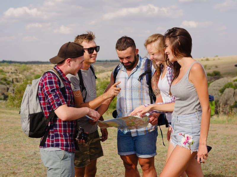 Turistas que miran una correspondencia Mapa de la demostración de la guía a los estudiantes que viajan en un fondo natural Concep fotografía de archivo