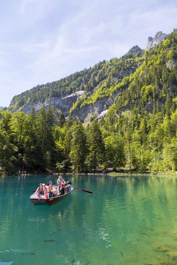 Turistas que montam no barco em Blausee ou no parque natural azul do lago no verão, Kandersteg, Suíça fotografia de stock royalty free