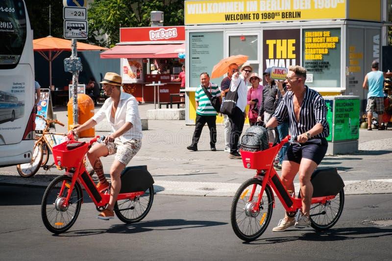 Turistas que montan la bici eléctrica que comparte las bicicletas, SALTO por UBER en la calle en Berlín fotos de archivo