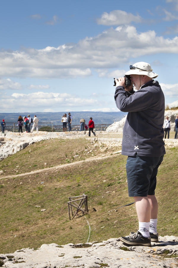 Turistas que olham com o anfiteatro romano dos binóculos Siracusa, Sicília Italy foto de stock