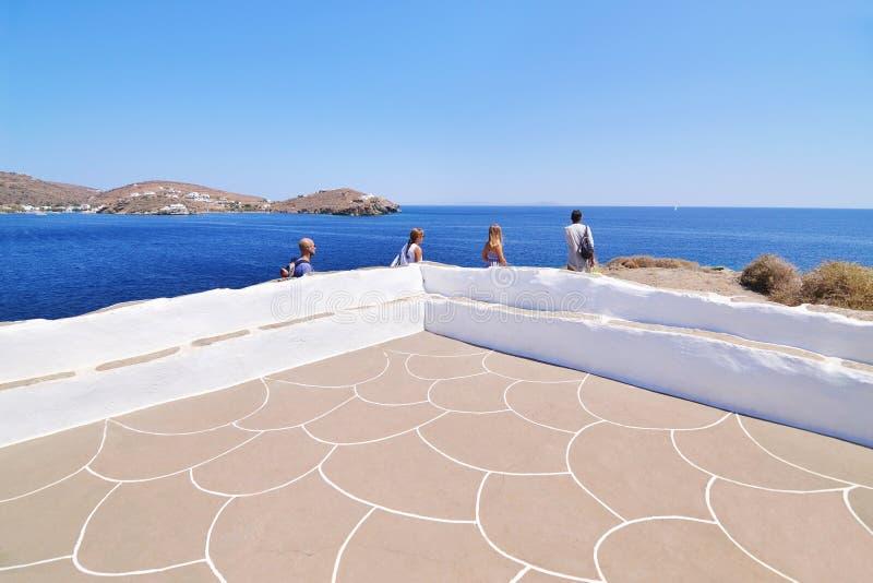 Turistas que olham o Mar Egeu na igreja Sifnos Grécia de Panaghia Chrisopigi fotografia de stock royalty free
