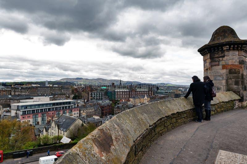 Turistas que pasan por alto la vista escénica de la ciudad de Edimburgo de la explanada delante del Gatehouse, castillo de Edimbu imagen de archivo