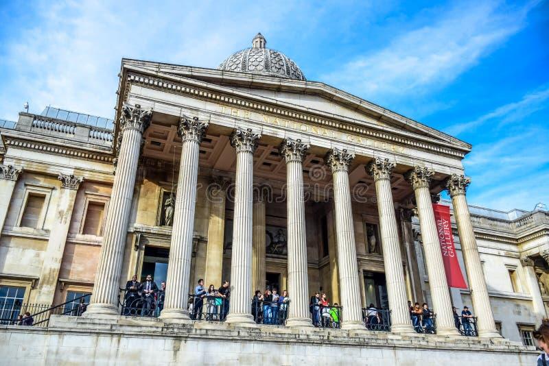 Turistas que penduram para fora na entrada do museu do National Gallery em Trafalgar Square em Londres, Inglaterra, Reino Unido imagem de stock royalty free
