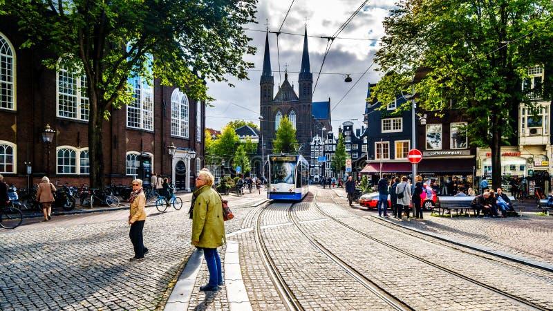 Turistas que recolectan en el cuadrado de Spui Plein Spui en el centro histórico de Amsterdam con la iglesia de Kruitberg en el f fotografía de archivo libre de regalías