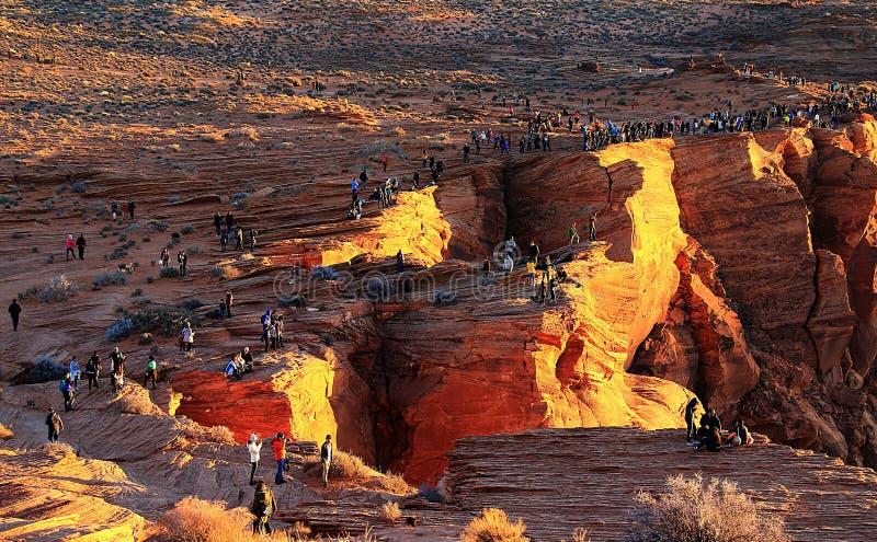 Turistas que se colocan al borde de los acantilados en la curva de herradura en la página, Arizona imágenes de archivo libres de regalías
