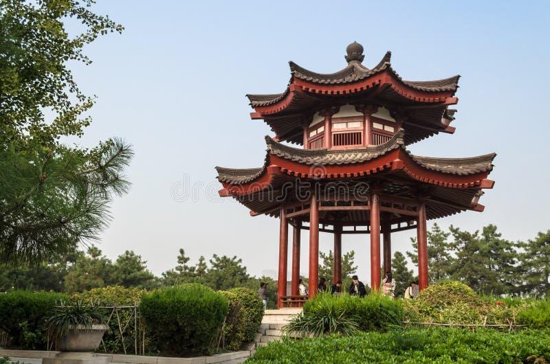 Turistas que se sientan debajo de una pagoda budista en el territorio de la pagoda salvaje gigante del ganso, Xian, China imagenes de archivo