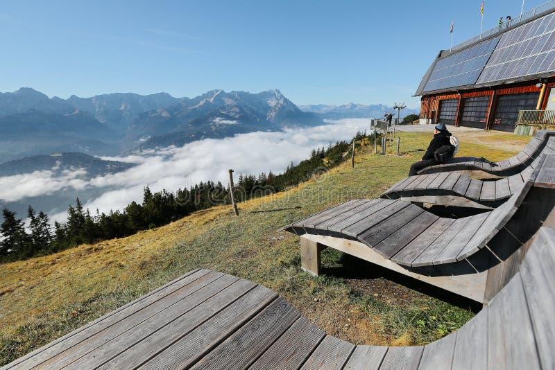 Turistas que se sientan en banco de madera y que disfrutan del panorama hermoso de la montaña de Zugspitze imagenes de archivo