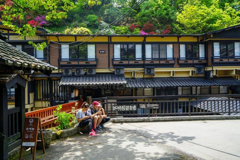 Turistas que se sientan en el pote de la planta en la calle con el carril, los edificios locales y la vista de flores floreciente fotografía de archivo