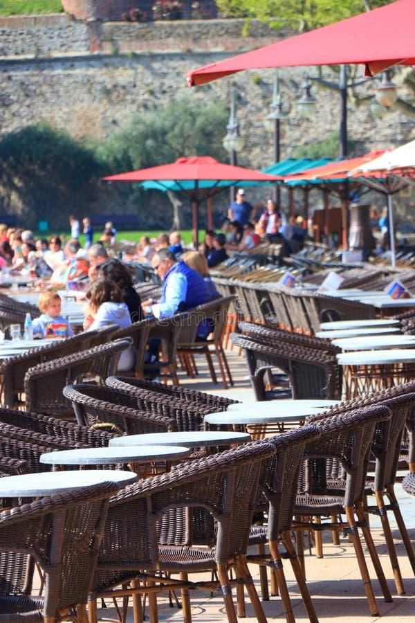 Turistas que se sientan en la terraza de un café francés en Collioure, Francia imagen de archivo