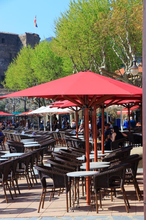 Turistas que se sientan en la terraza de un café francés en Collioure, Francia fotos de archivo