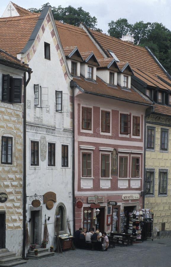 Turistas que se sientan fuera de un pequeño restaurante en Cesky Krumlov, República Checa Cesky Krumlov es una de las ciudades má foto de archivo libre de regalías