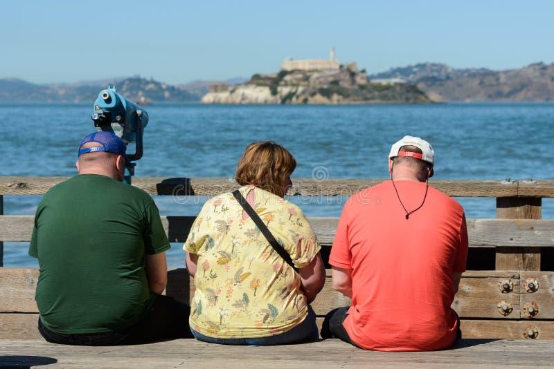Turistas que sentam-se em um banco com vistas da ilha e da prisão de Alcatraz no fundo do cais 39 em San Francisco imagens de stock