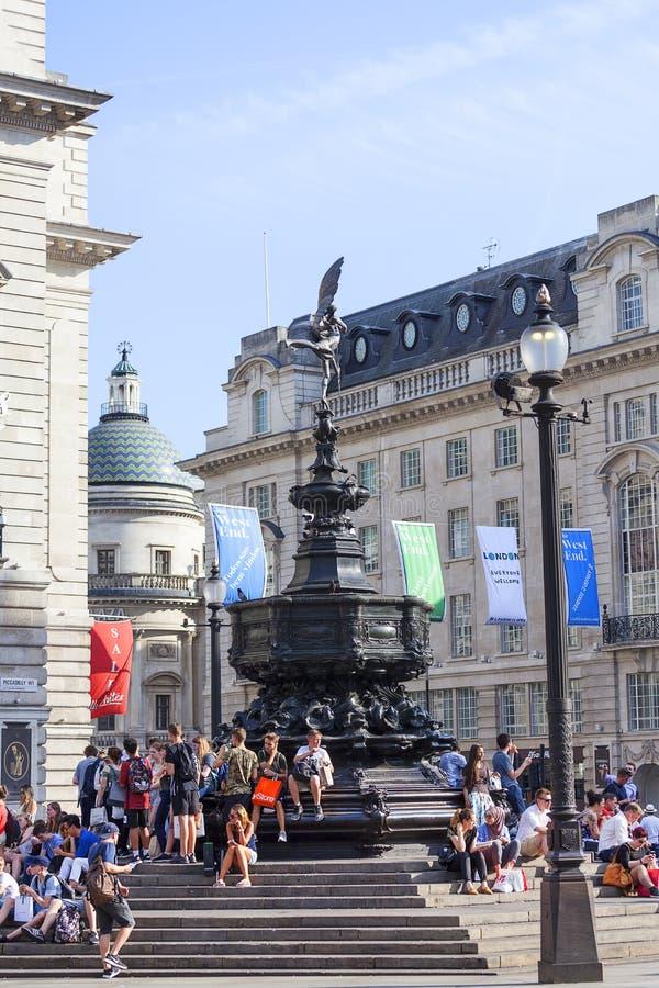 Turistas que sentam-se nas etapas da fonte memorável de Shaftesbury, circo de Piccadilly, Londres, Reino Unido imagens de stock royalty free