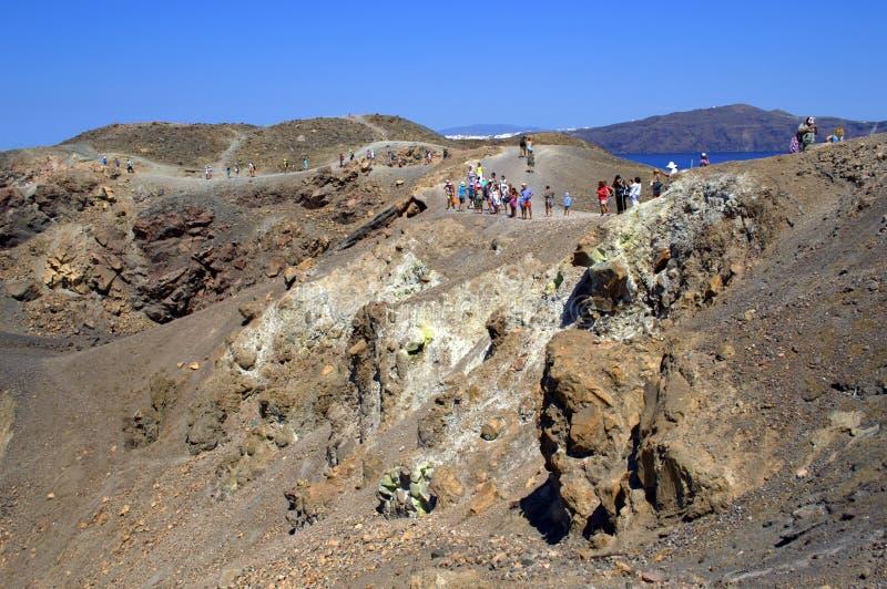 Turistas que surpreendem a cratera Nea Kameni do vulcão imagem de stock