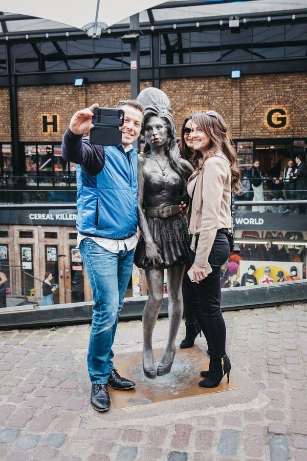Turistas que tomam fotos com a estátua de Amy Winehouse em Camden, Londres, Reino Unido fotografia de stock royalty free
