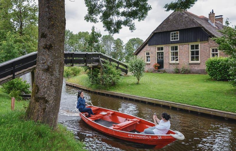 Turistas que tomam imagens em um barco em Giethoorn, Países Baixos foto de stock royalty free