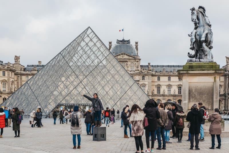 Turistas que tomam imagens na parte dianteira no museu do Louvre em Paris, França fotos de stock royalty free
