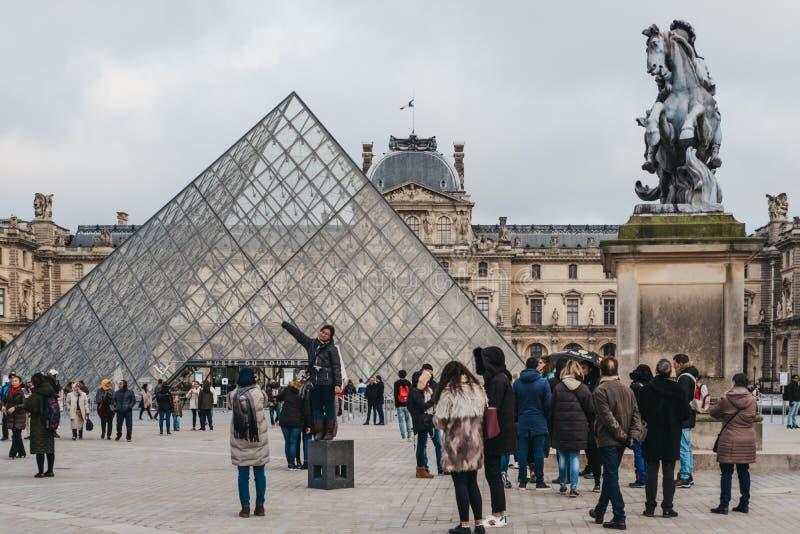 Turistas que tomam imagens na parte dianteira no museu do Louvre em Paris, França fotos de stock