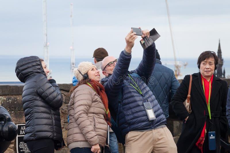 Turistas que tomam imagens panorâmicos em Edimburgo, Escócia fotografia de stock