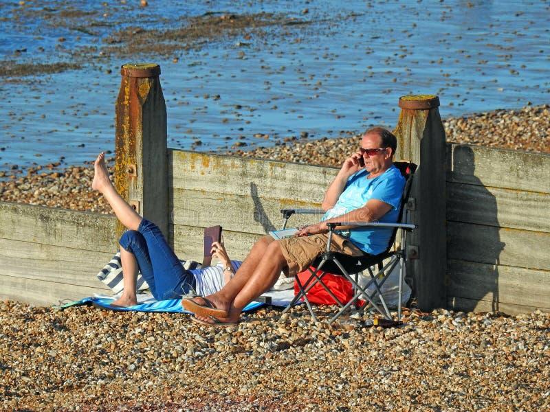 Turistas que toman el sol en la playa fotos de archivo