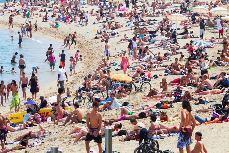 Turistas que toman el sol en la playa en Barcelona fotos de archivo