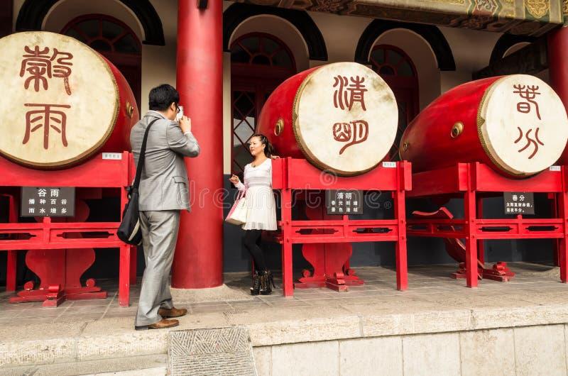 Turistas que toman imágenes en el teléfono móvil en el fondo de los tambores en el campanario en Xian fotografía de archivo