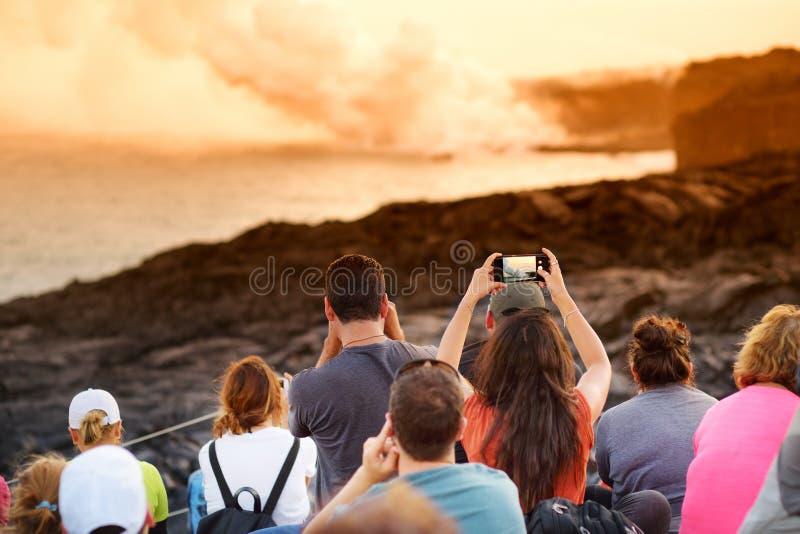 Turistas que toman las fotos en el área de visión de la lava de Kalapana Lava que vierte en el océano que crea un penacho venenos imágenes de archivo libres de regalías