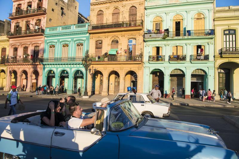 Turistas que toman las fotos en el coche clásico de la calle con arquitectura colonial, La Habana, Cuba imagen de archivo