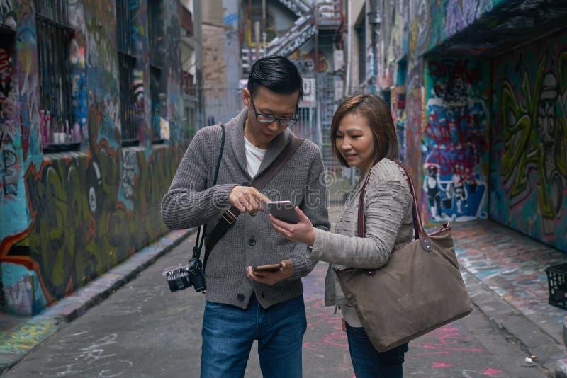 Turistas que usan el mapa en el dispositivo digital fotografía de archivo libre de regalías