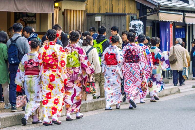 Turistas que vestem o quimono tradicional japonês que anda em Arashiyama, Kyoto em Japão fotos de stock royalty free