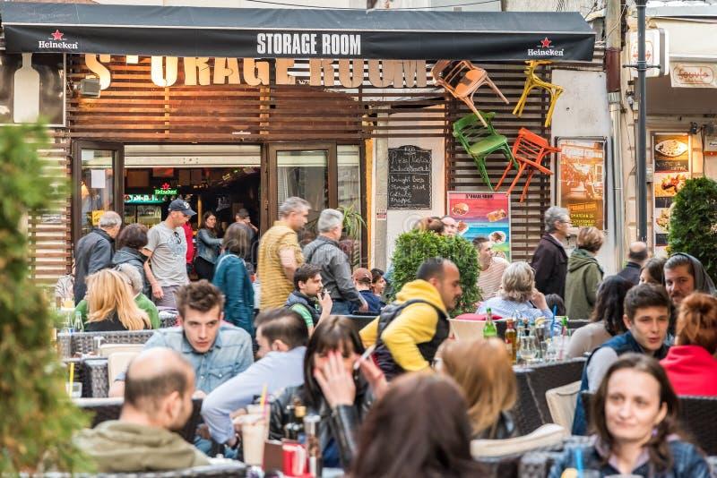 Turistas que visitam e que têm o almoço na baixa exterior do café do restaurante em Bucareste fotografia de stock