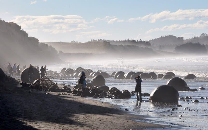 Turistas retroiluminados en los cantos rodados de Moeraki, Nueva Zelandia imagen de archivo