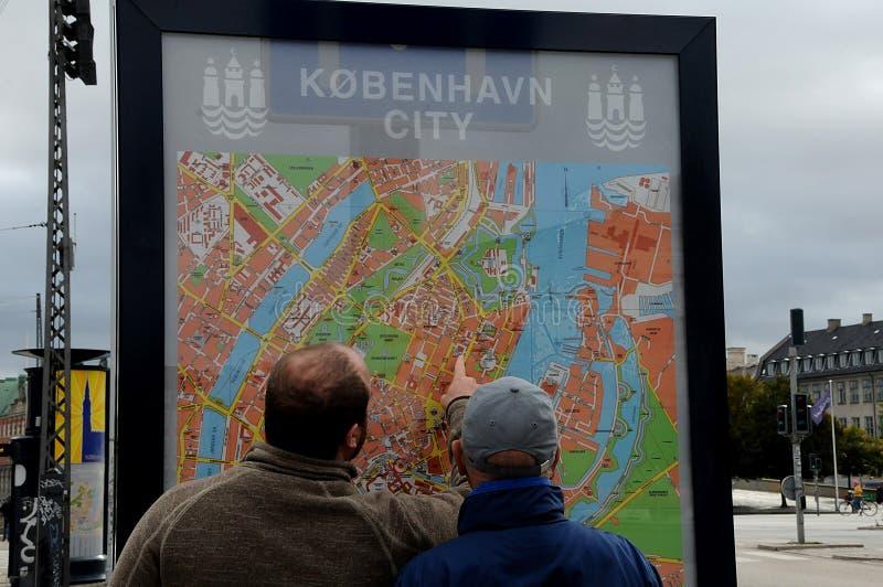 Turistas studing el mapa de la ciudad en Copenhague Dinamarca imagen de archivo