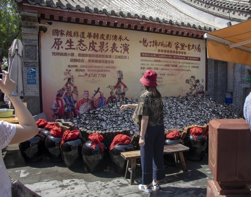 Turistas supersticiosos que despedaçam copos no valor intangível de Yongxingfang foto de stock