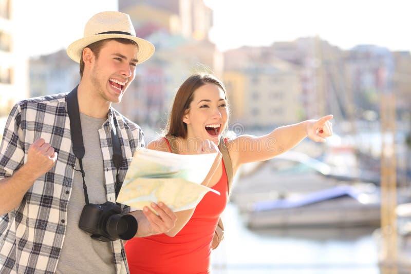 Turistas surpreendidos que encontram e que apontam o marco imagem de stock