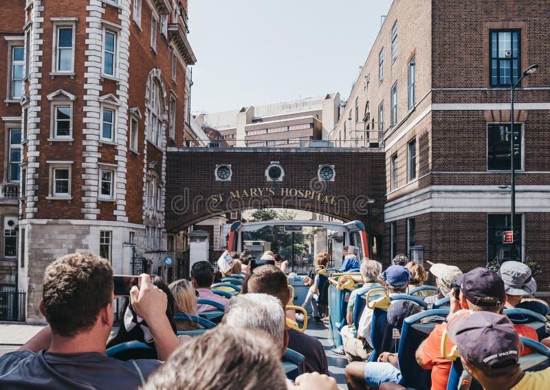 Turistas tirando fotos do andar de cima de um ônibus turístico em Londres, Reino Unido imagens de stock