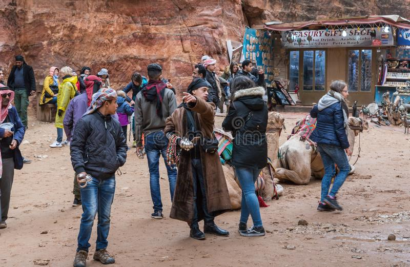 Turistas, vendedores e motoristas - beduínos, camelos e lojas de lembrança beduínas no quadrado na frente de PETRA perto da cidad fotos de stock royalty free