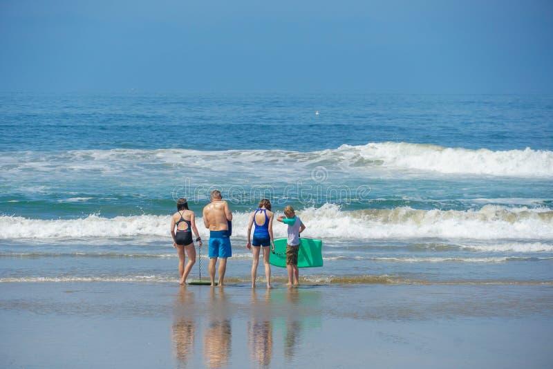 Turistas y familias en la playa que disfrutan de día de verano hermoso fotos de archivo