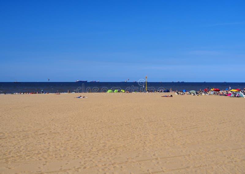 Turistas y gente de vacaciones en el Mar del Norte en la playa de Scheveningen en un día de verano soleado fotos de archivo libres de regalías