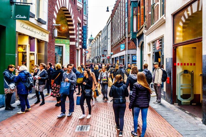 Turistas y locals en la calle ocupada de las compras de Niewendijk en el centro histórico de Amsterdam imagen de archivo libre de regalías