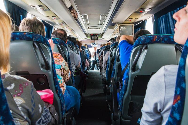 Turistas y un guía turístico masculino con un micrófono en el autobús imagen de archivo