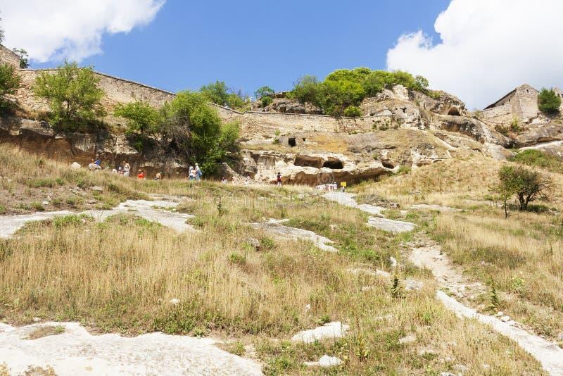 Turistas y viajeros en la pared externa de la col rizada de Chufut de la ciudad de la cueva imagenes de archivo