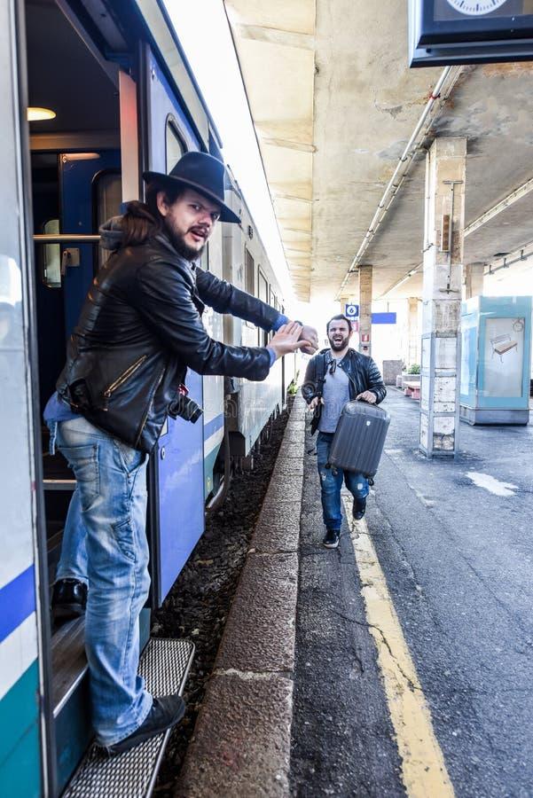 Turisten är tokig, därför att hans vän släpar sig efter drevet royaltyfri foto