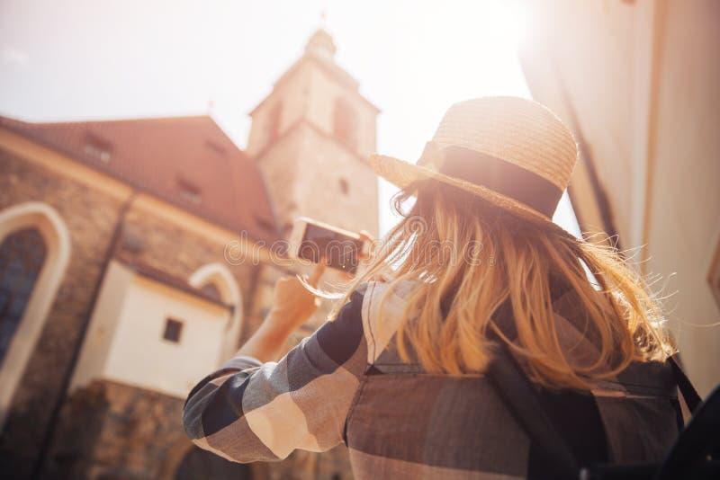 Turisten för den unga kvinnan i sugrörhatt och med ryggsäcken använder telefonen som kameran som tar bilder av byggnader fotografering för bildbyråer