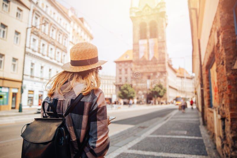 Turisten för den unga kvinnan i sugrörhatt och ryggsäck använder telefonen som navigatör till och med gator av Europa royaltyfria bilder