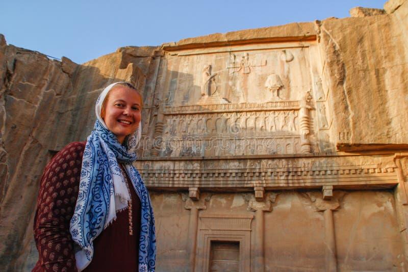 Turisten för den unga kvinnan med ett täckt huvud står på bakgrunden av de berömda basrelieferna av daghuvudstaden av Persia Iran royaltyfri bild