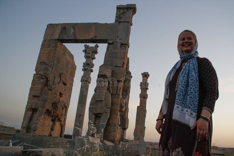 Turisten för den unga kvinnan med ett täckt huvud står på bakgrunden av de berömda basrelieferna av daghuvudstaden av Persia Iran arkivbilder