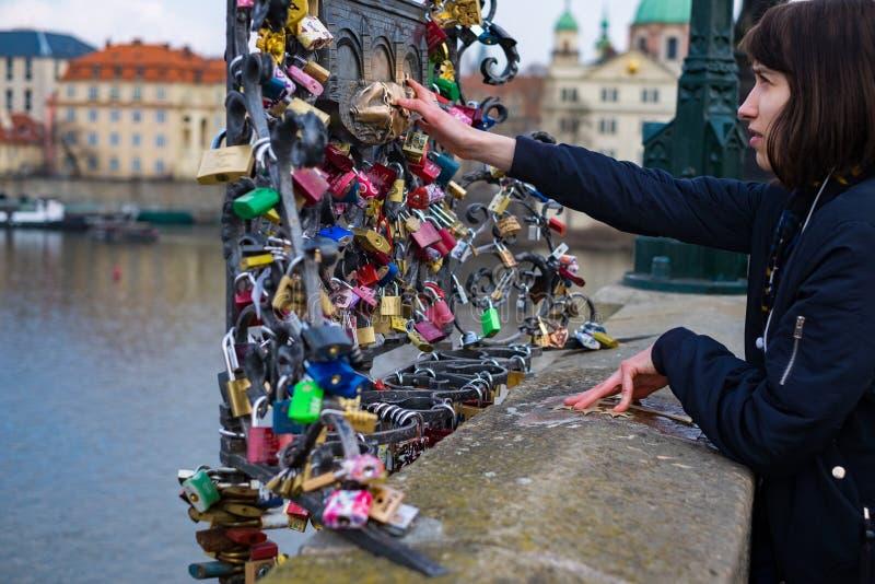 Turisten för den unga kvinnan trycker på statyn av St John Nepomuk på den Charles bron som det finns många lås på, som hänger för arkivfoton
