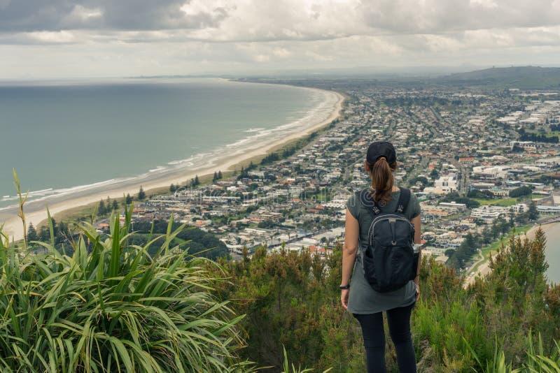 Turisten för den unga kvinnan tycker om havsikten i Mt Maunganui arkivbilder
